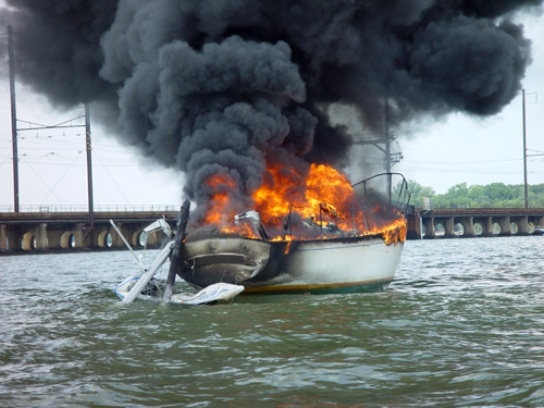 """Dramatic image of large (~40') sailboat which burned after having come in contact with overhead electrical lines. Maryland, USA"""